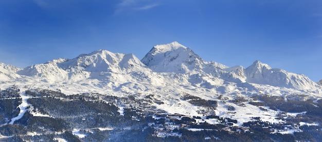 Vista sulla montagna di punta coperta di neve in inverno sopra la stazione sciistica nelle alpi europee