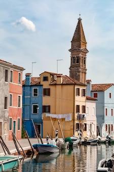 Vista sulla strada vuota con le barche nel canale d'acqua, case colorate tipiche e antica torre nell'isola di burano, italia