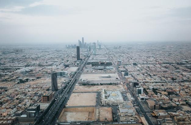 Vista sullo skyline di riyad in direzione del king abdullah financial district dalla cima della torre del regno di riyadh nella nebbiosa giornata nuvolosa