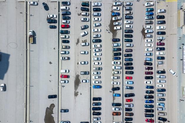 Vista superiore aerea del parcheggio con molte automobili da sopra, trasporto e concetto urbano. colpo di drone in elicottero.