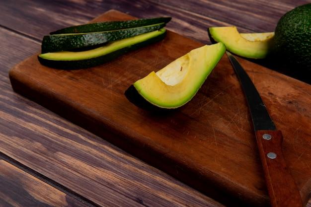 Vista superiore affettato avocado con coltello sul tagliere sul tavolo di legno