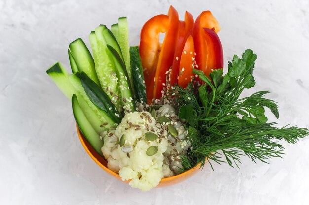 Vista superiore ciotola con fette di verdura - cetriolo, pepe, cavolfiore, sesamo, aneto, semi di zucca