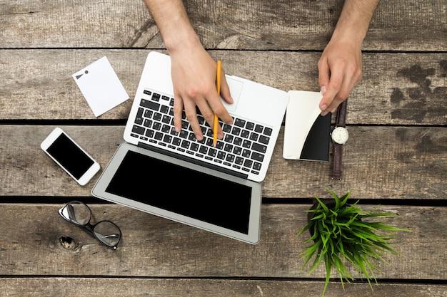 Vista superiore da tavolino di legno dei pantaloni a vita bassa rustici, mani maschii facendo uso del computer portatile