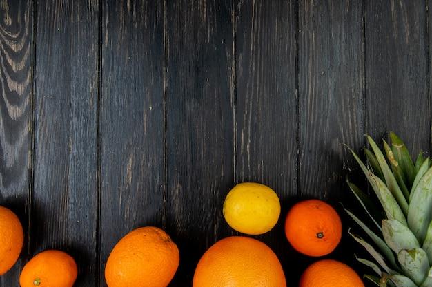 Vista superiore degli agrumi come ananas del pompelmo del limone del mandarino su fondo di legno con lo spazio della copia