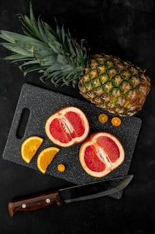 Vista superiore degli agrumi come ananas e kumquat arancio del pompelmo con il coltello sul tagliere su superficie nera