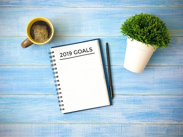 Vista superiore degli obiettivi di scrittura del taccuino 2019 anni sulla tavola di legno blu.