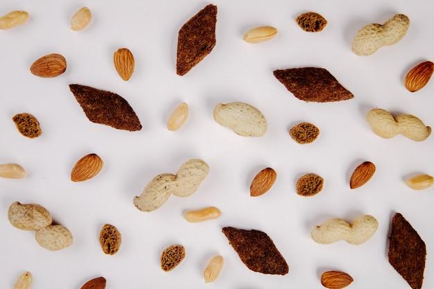 Vista superiore degli spuntini arachidi della mandorla con buccia e senza buccia e cracker piccanti su bianco