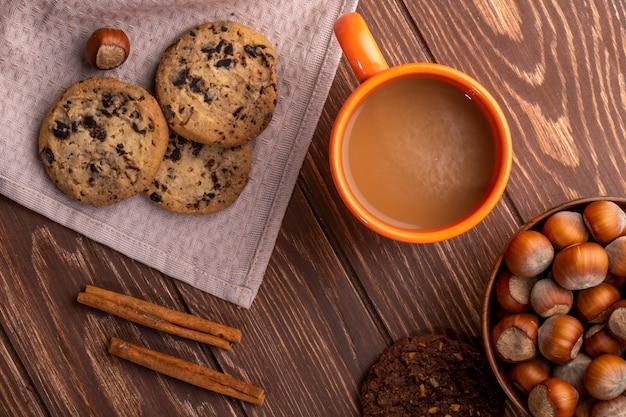Vista superiore dei biscotti di farina d'avena con gocce di cioccolato e cacao e una tazza con bevanda al cacao su un legno