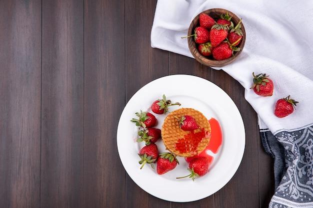 Vista superiore dei biscotti e delle fragole della cialda in piatto e ciotola di fragole sul panno su superficie di legno