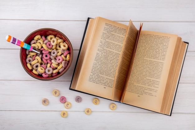 Vista superiore dei cereali multicolori e sani su una ciotola rossa con i cereali isolati su superficie bianca