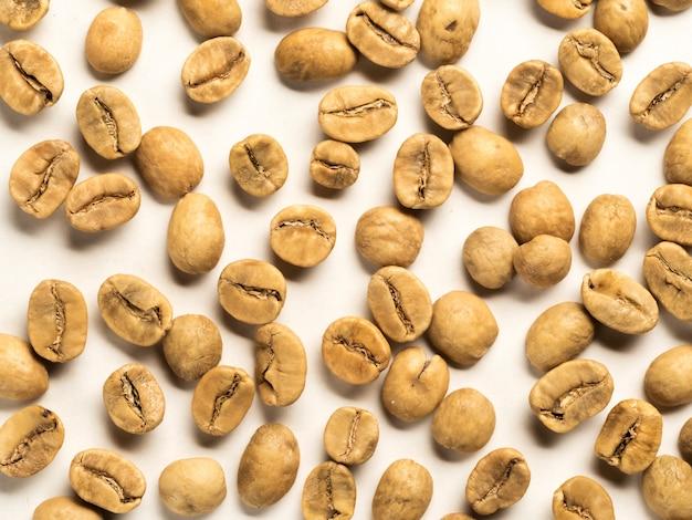 Vista superiore dei chicchi di caffè bianco su fondo bianco