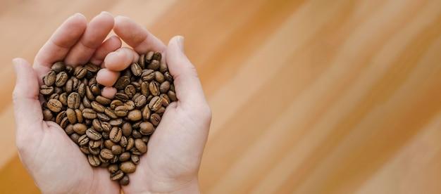 Vista superiore dei chicchi di caffè della tenuta di barista in mani in forma di cuore con lo spazio della copia