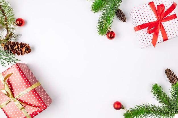 Vista superiore dei contenitori di regalo fatti a mano di natale con i nastri, i rami di pino con i coni e i giocattoli su bianco