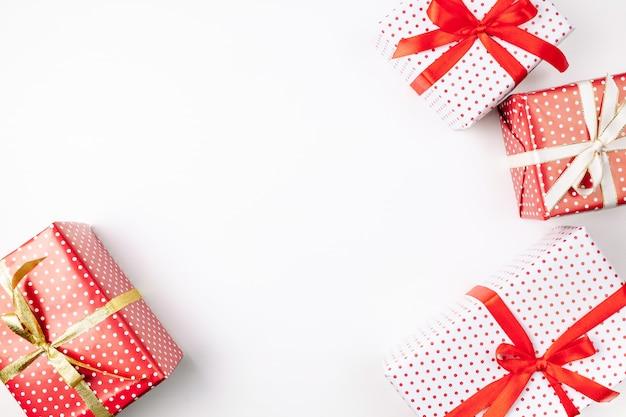 Vista superiore dei contenitori di regalo fatti a mano di natale con i nastri su bianco