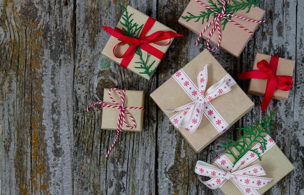 Vista superiore dei contenitori di regalo fatti a mano di natale su fondo di legno rustico