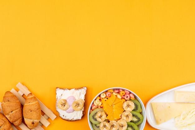 Vista superiore dei croissant con lo spazio del formaggio, del pane tostato e della copia di frutti sull'orizzontale giallo del fondo