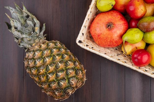 Vista superiore dei frutti come merce nel carrello della mela della prugna della pesca del melograno con l'ananas su superficie di legno