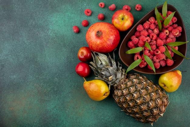 Vista superiore dei frutti come prugna della pesca della mela del melograno dell'ananas con il canestro del lampone su superficie verde