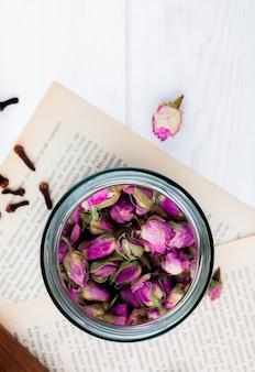 Vista superiore dei germogli di rosa del tè secco in un barattolo di vetro alle pagine del libro