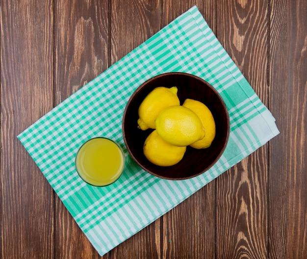 Vista superiore dei limoni in ciotola con bicchiere di succo di limone sul panno e sul fondo di legno