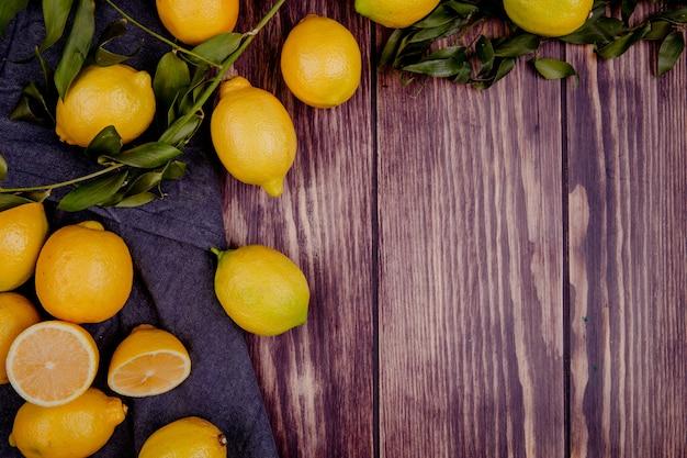 Vista superiore dei limoni maturi freschi isolati su rustico con lo spazio della copia