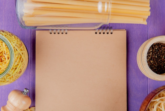 Vista superiore dei maccheroni come bucatini degli spaghetti con pepe nero intorno al blocco note su fondo porpora con lo spazio della copia