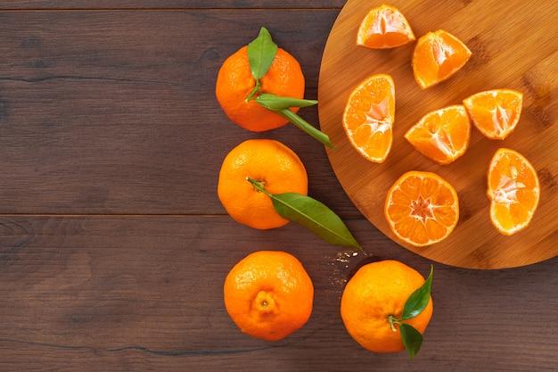 Vista superiore dei mandarini freschi con lo spazio della copia sul tagliere di legno