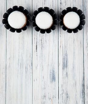 Vista superiore dei muffin deliziosi dolci con i fiocchi della noce di cocco isolati su fondo rustico con lo spazio della copia