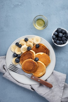 Vista superiore dei pancake della prima colazione sul piatto con i mirtilli e le fette della banana