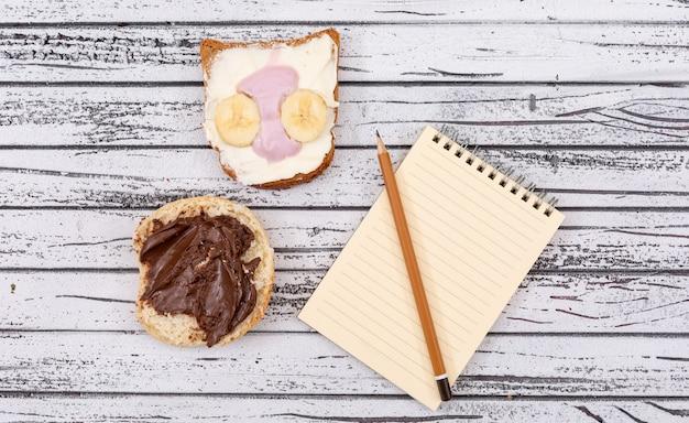 Vista superiore dei pani tostati con lo spazio della copia sul taccuino sull'orizzontale di superficie di legno bianco