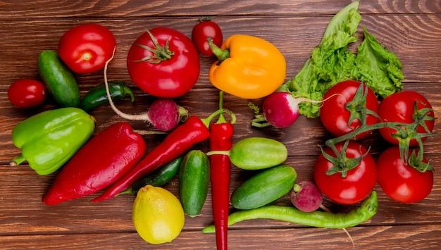 Vista superiore dei peperoncini rossi e della lattuga variopinti dei pomodori dei cetrioli dei ravanello dei peperoni dolci degli ortaggi freschi su legno rustico
