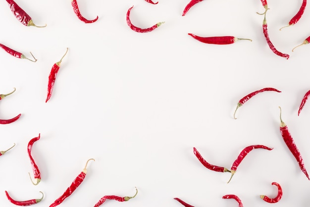 Vista superiore dei peperoncini secchi rossi con lo spazio della copia su superficie bianca