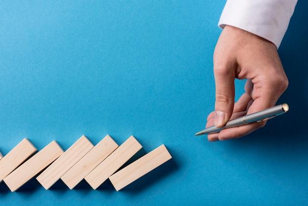 Vista superiore dei pezzi di domino e della penna di tenuta dell'uomo d'affari