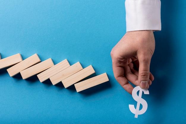 Vista superiore dei pezzi e dell'uomo d'affari di domino che tengono simbolo di dollaro