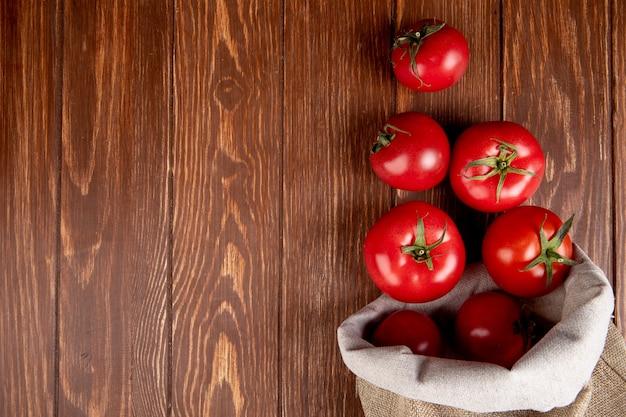 Vista superiore dei pomodori che si rovesciano dal sacco dalla destra e dal legno con lo spazio della copia