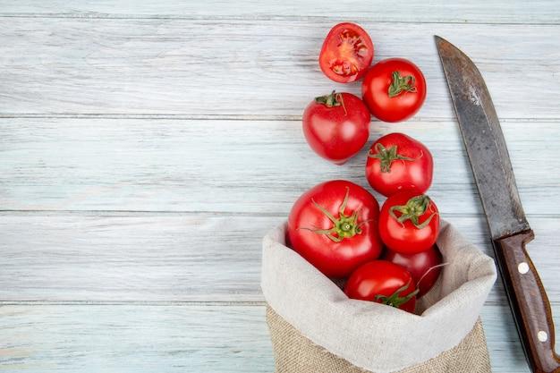 Vista superiore dei pomodori che si rovesciano dal sacco e dal coltello su superficie di legno con lo spazio della copia