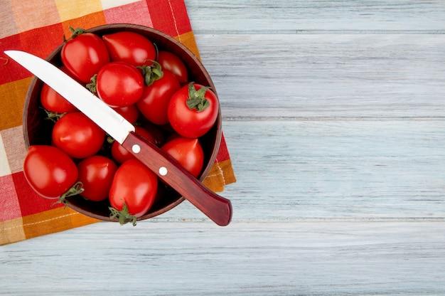 Vista superiore dei pomodori con il coltello in ciotola sul panno e sul legno con lo spazio della copia