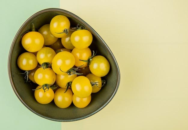 Vista superiore dei pomodori gialli in ciotola sulla tavola gialla e verde
