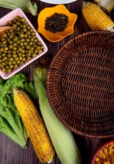Vista superiore dei semi con piselli pepe nero e lattuga su superficie di legno