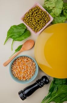 Vista superiore dei semi secchi del cereale con la lattuga degli spinaci dei piselli e il piatto vuoto su bianco