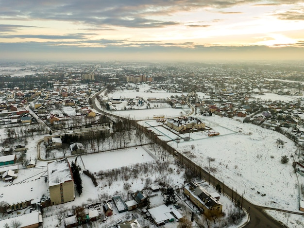 Vista superiore dei sobborghi della città o delle case piacevoli della cittadina sulla mattina di inverno sul fondo del cielo nuvoloso. concetto di fotografia aerea drone.