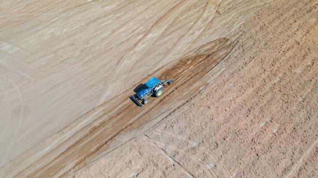 Vista superiore dei veicoli del trattore agricolo che lavorano al campo