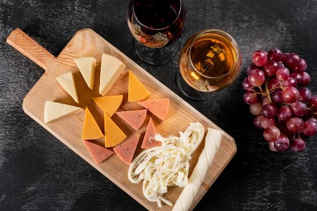 Vista superiore dei vetri e del formaggio di vino sul tagliere di legno sull'orizzontale scuro