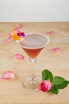 Vista superiore del bicchiere da cocktail decorato in piedi su un tavolo vuoto con rosa fresca sul fondo
