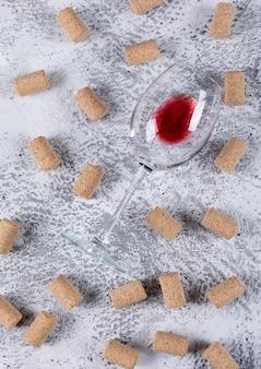 Vista superiore del bicchiere di vino con tappi di sughero sul verticale di pietra bianca