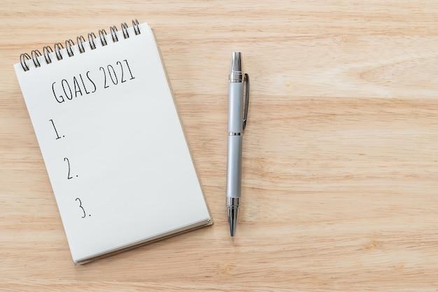 Vista superiore del blocco note con la lista di obiettivi sulla tavola di legno, concetto di obiettivi.
