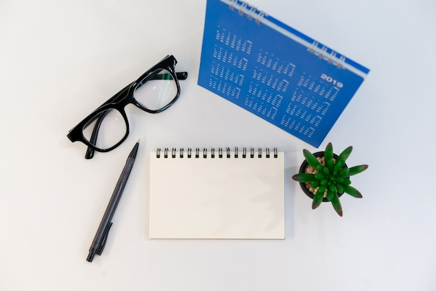 Vista superiore del blocco note vuoto, matita, occhiali, calendario e piccola pianta sul tavolo