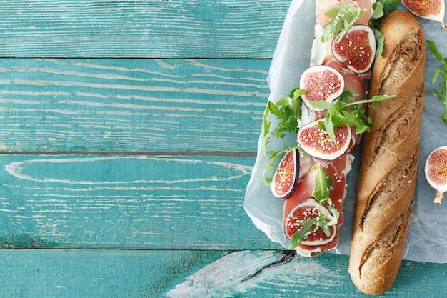 Vista superiore del bordo di legno della tavola dei fichi del mascarpone del prosciutto di parma del panino