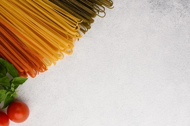Vista superiore del bordo vegetariano degli ingredienti della pasta. spaghetti, pomodoro e spaghetti classici con pomodorini e basilico su fondo di pietra bianca con spazio di copia.