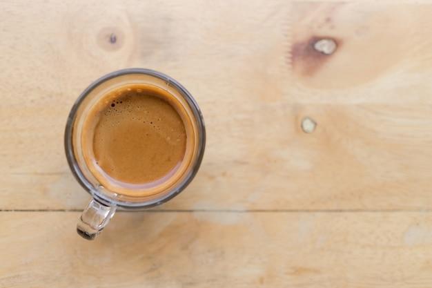 Vista superiore del caffè espresso fresco del caffè in una tazza di caffè sulla tavola di legno nel caffè, immagine con lo spazio della copia.